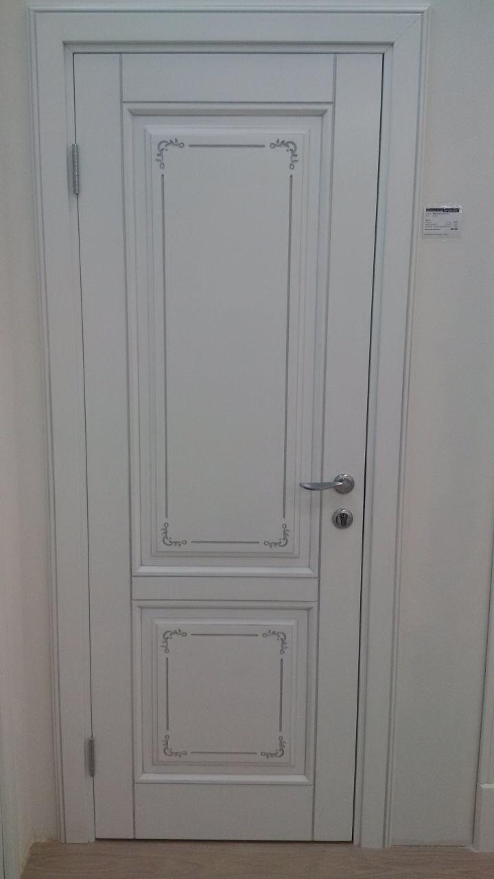 белая дверь с фигурным наличником