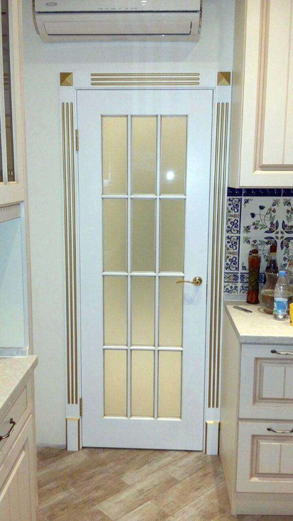 фото межкомнатная белая дверь со стеклом и с золотой патиной
